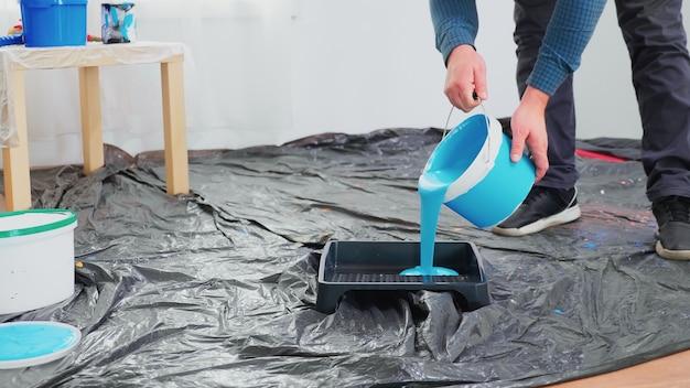 Man die blauwe verf uit blik giet voor huisrenovatie. appartement herinrichting en woningbouw tijdens renovatie en verbetering. reparatie en decoreren.