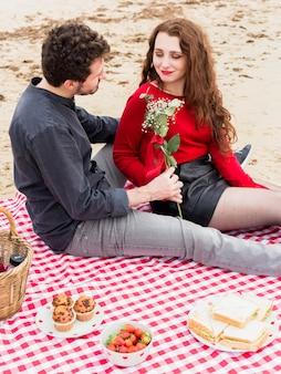 Man die bloemen geeft aan de vrouw op geruite dekbed