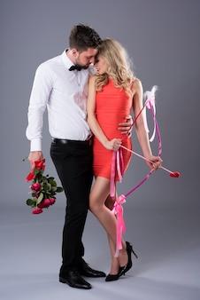 Man die bloemen geeft aan zijn vrouwelijke cupido