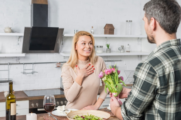 Man die bloemen voorstelt aan verraste vrouw in keuken