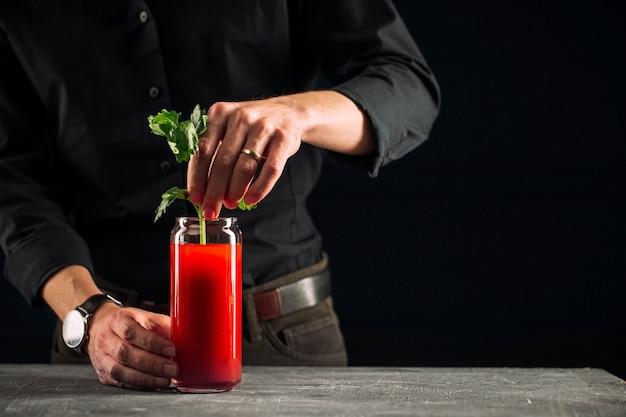Man die bloody mary cocktail met selderij maakt
