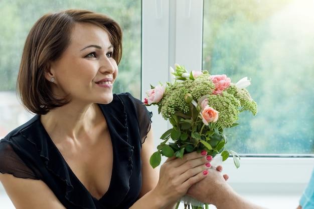 Man die boeket van bloemen en verrast vrouw geeft