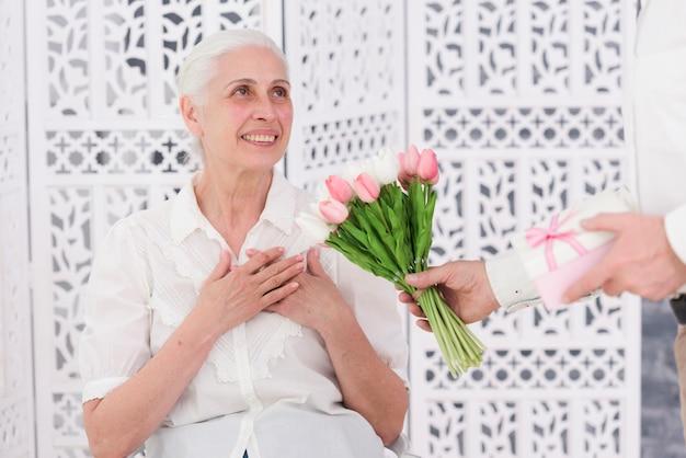 Man die boeket van tulpenbloemen en giftdoos geeft aan zijn gelukkige vrouw op haar verjaardag