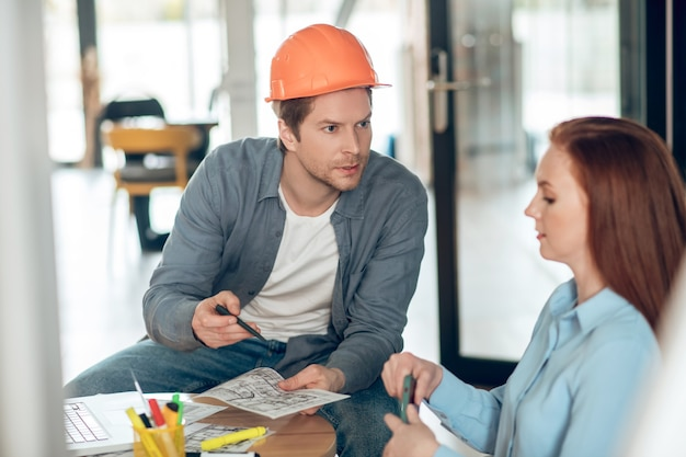 Man die bouwplan toont aan serieuze vrouw