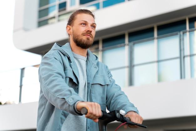Man die buiten op een milieuvriendelijke scooter rijdt