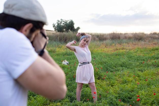 Man die camerafoto's van een vrouw in het veld neemt Premium Foto