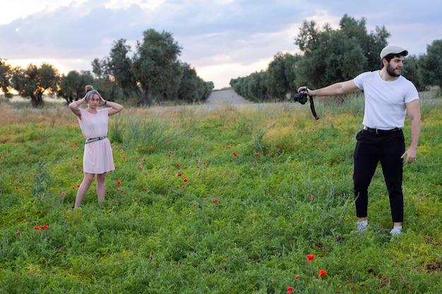 Man die camerafoto's van een vrouw in het veld neemt