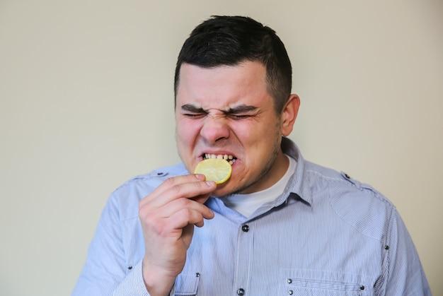 Man die citroen eet. wince van zure smaak.