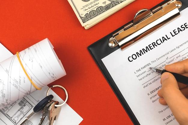 Man die commerciële huurovereenkomst invult. klembord met bedrijfsdocument, huissleutels, pen en geld. rode achtergrond, kopieer ruimtefoto