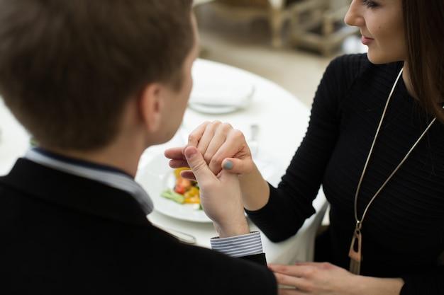 Man die de hand van een vrouw kust tijdens een romantisch diner terwijl ze naar hem kijkt met een bewonderende uitdrukking en een mooie glimlach