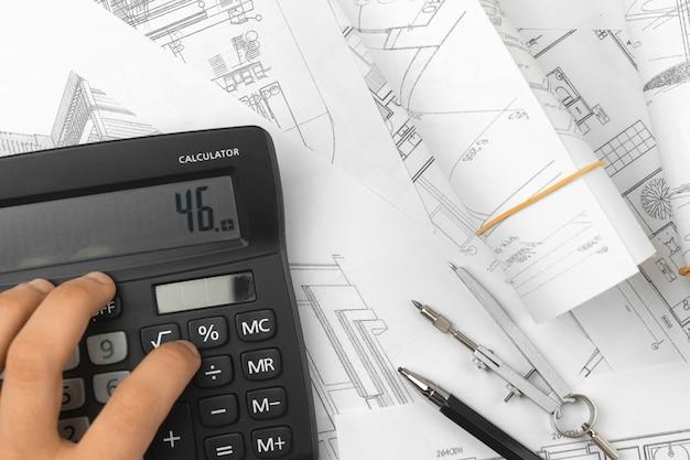 Man die de kosten berekent van het werken met architectenontwerp, achtergrond van het tekenen van schetsplannen blauwdrukken