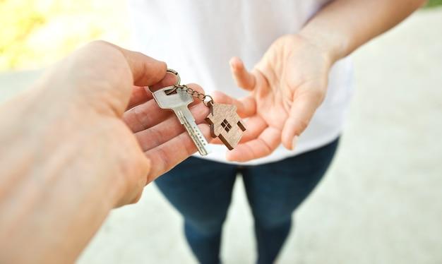 Man die de metalen sleutel van deur met houten trinket in vorm van huis aan de vrouw geeft