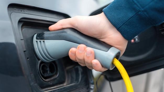 Man die de oplader aansluit op een elektrische auto bij het laadstation