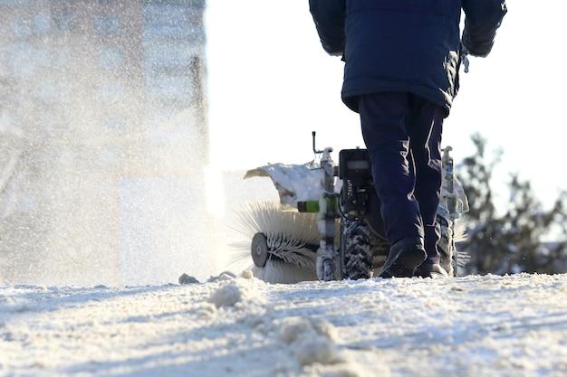 Man die de straat schoonmaakt van sneeuw handmatige tractor speciaal