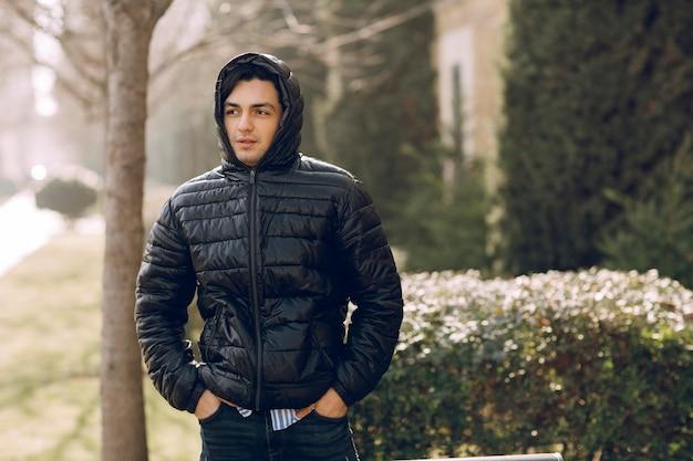 Man die de zwarte leren jas tot het einde dichtritst en de hoodie draagt om kou te voorkomen. hoge kwaliteit foto