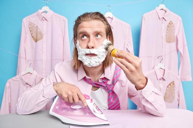 Man die diep in gedachten is terwijl hij zich aan het scheren concentreert druk bezig met het strijken van kleding bereidt zich voor op een speciale gelegenheid wil een briljante uitstraling hebben poseert in de buurt van verveeld in de buurt van gestreken shirts