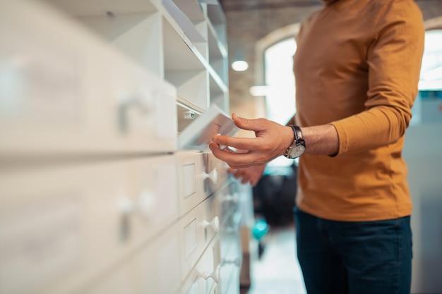 Man die doos opent. close-up van een man met een oranje polohals en een horloge bij de hand die de doos opent