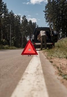 Man die driehoekswaarschuwingsbord op de weg zet na autopech