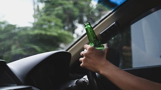 Man die een auto bestuurt en een flesje bier vasthoudt. niet drinken en rijden concept.