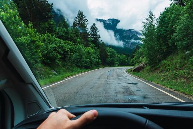 Man die een auto bestuurt op de weg in de pyreneeën