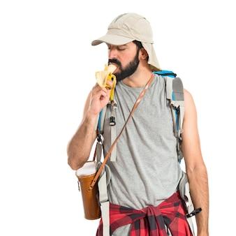 Man die een banaan over witte achtergrond eet