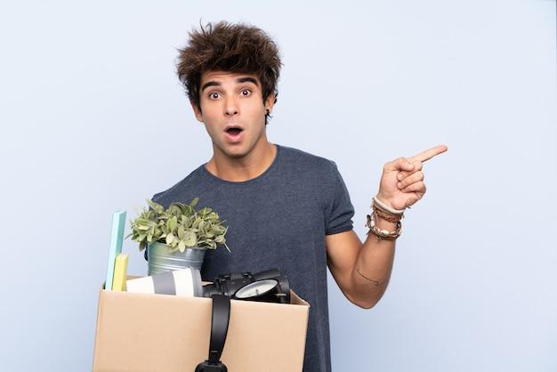 Man die een beweging maakt terwijl hij een doos vol dingen oppakt die verrast zijn en zijn vinger naar de zijkant wijst