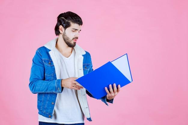 Man die een blauwe map opent en deze controleert