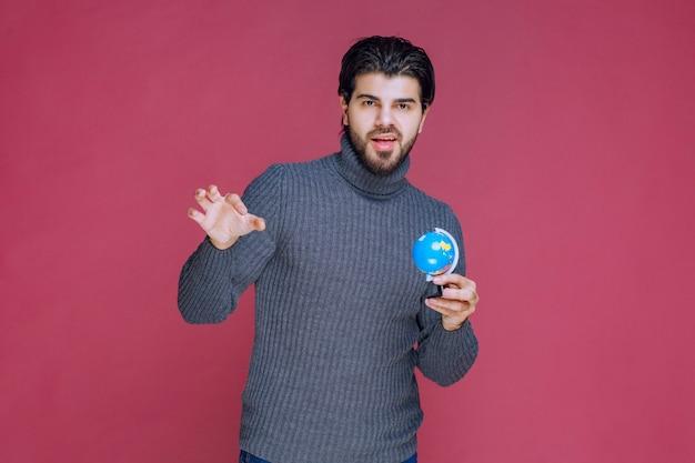 Man die een blauwe mini-wereldbol vasthoudt en deze demonstreert aan de menigte.