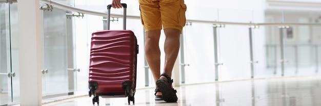 Man die een bordeauxrode koffer op de vloer trekt bij de luchthavenclose-up