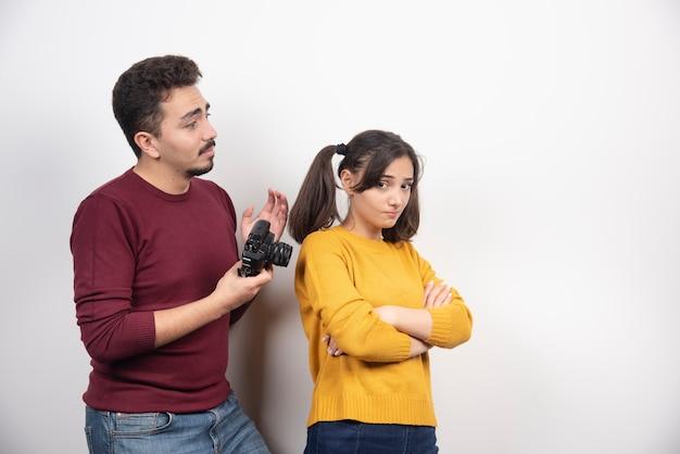 Man die een camera houdt en op jonge vrouw kijkt.