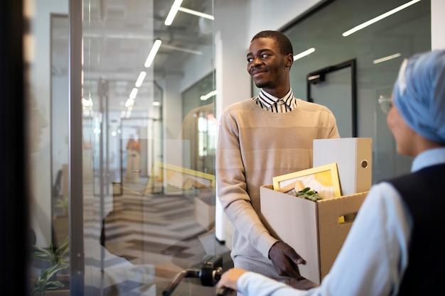 Man die een doos met spullen vasthoudt en zich vestigt in zijn nieuwe kantoorbaan