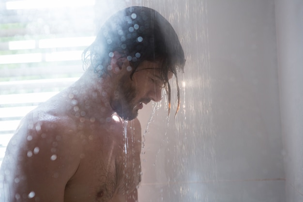 Man die een douche in de badkamer