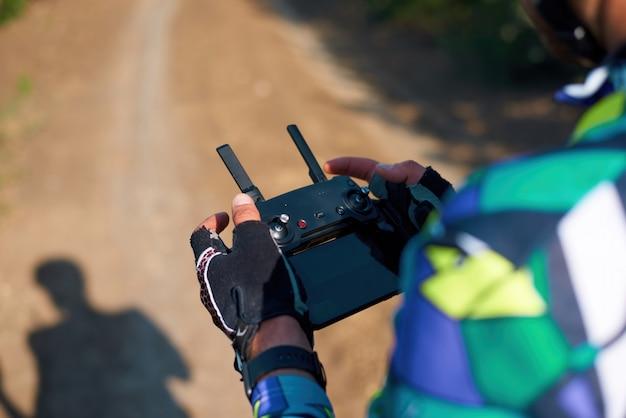 Man die een drone in het bos bestuurt