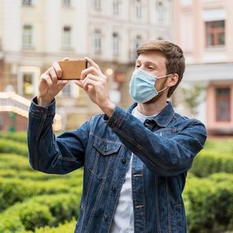Man die een foto neemt terwijl hij een gezichtsmasker draagt