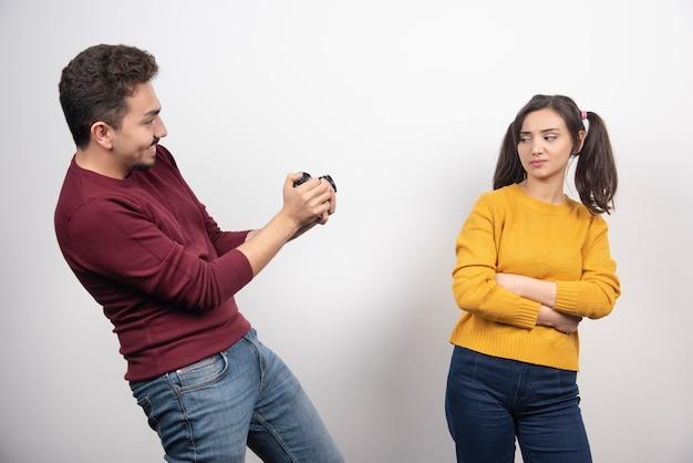 Man die een foto van een jonge vrouw op een witte muur.