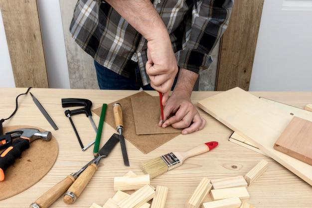 Man die een gat in hout timmerwerk workshop concept