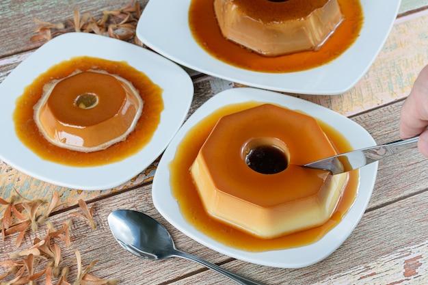 Man die een gecondenseerde melkpudding snijdt met karamelsiroop, omringd door andere puddingen, lepel en vliegende zaden (triplaris amaricana). traditioneel braziliaans snoepje.