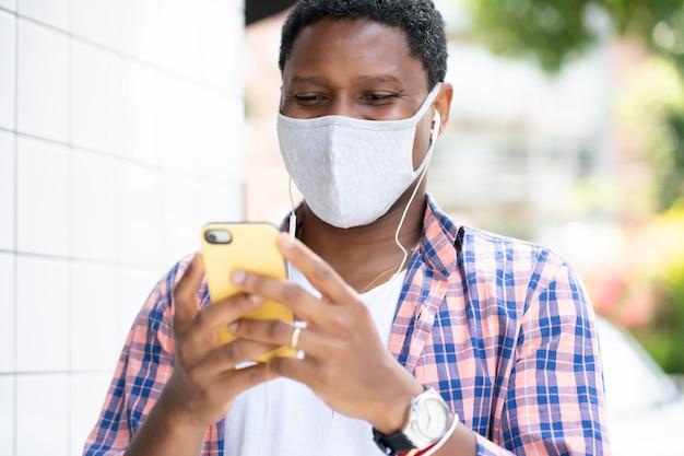 Man die een gezichtsmasker draagt en zijn mobiele telefoon gebruikt terwijl hij buiten staat. nieuw normaal levensstijlconcept.