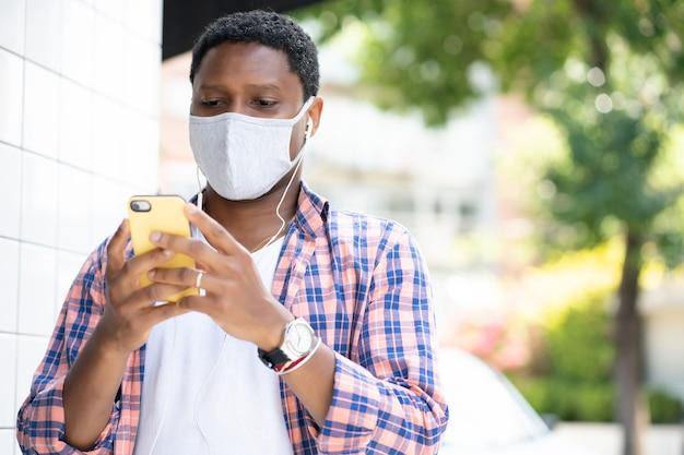 Man die een gezichtsmasker draagt en zijn mobiele telefoon gebruikt terwijl hij buiten staat