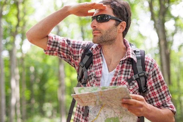 Man die een kaart in het bos controleert