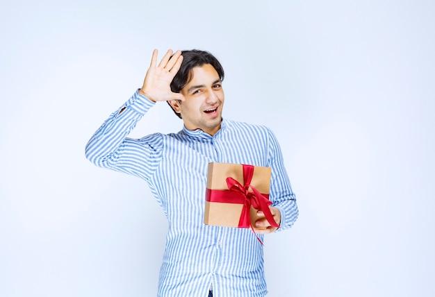 Man die een kartonnen geschenkdoos met rood lint vasthoudt en zijn dankbaarheid uitdrukt. hoge kwaliteit foto