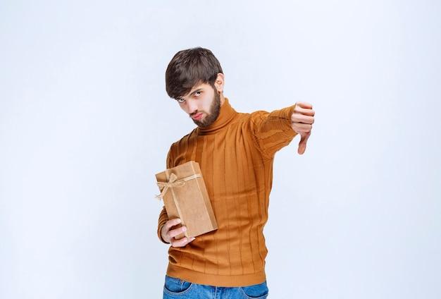 Man die een kartonnen geschenkdoos vasthoudt en er een hekel aan heeft.