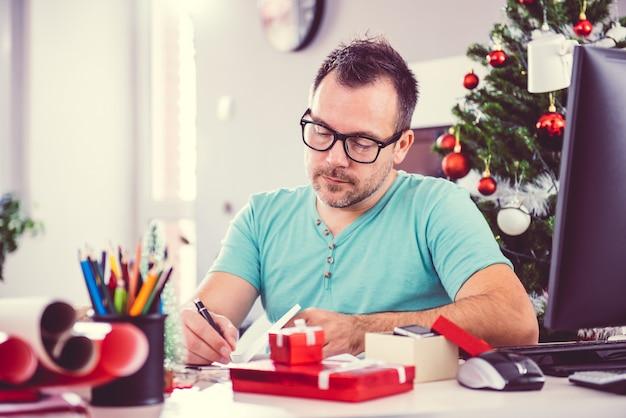 Man die een kerstkaart schrijft