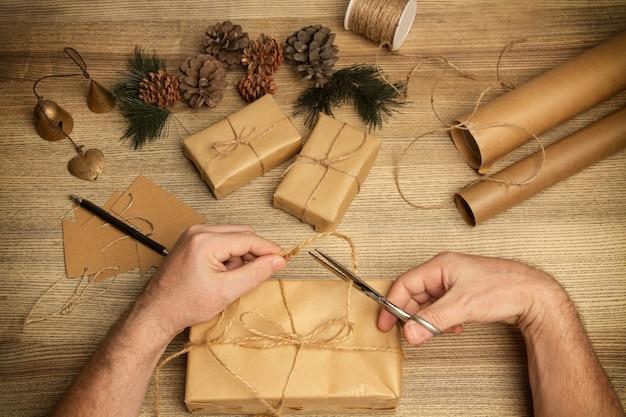Man die een kerstpakket maakt op een houten tafel in een bovenaanzicht