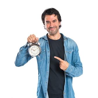 Man die een klok over witte achtergrond houdt