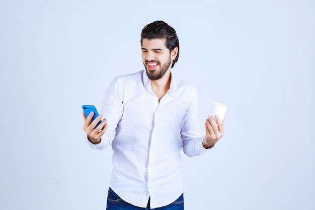 Man die een koffiekopje in de ene hand houdt en zijn telefoon in de andere hand controleert