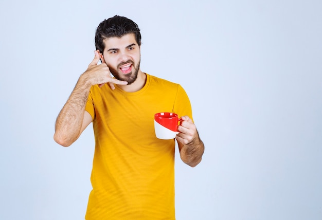 Man die een koffiekopje vasthoudt en om een telefoontje vraagt.