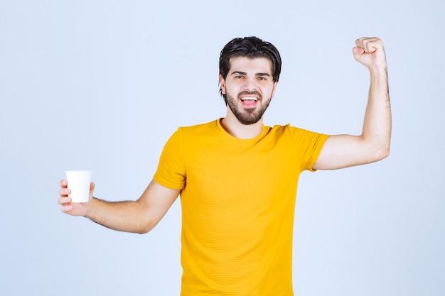 Man die een koffiekopje vasthoudt en zijn kracht laat zien.