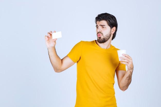 Man die een koffiekopje vasthoudt en zijn visitekaartje presenteert.