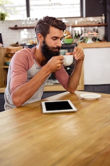 Man die een kopje koffie drinkt